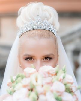 Primo piano della vista di una bellissima sposa in una preziosa corona con un bouquet tra le mani