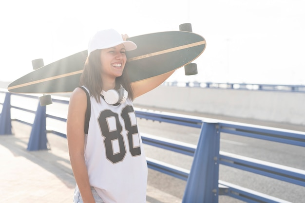 Close-up view of a beautiful girl with her long board skateboard at sunset