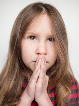 Vista del primo piano di bella preghiera della bambina