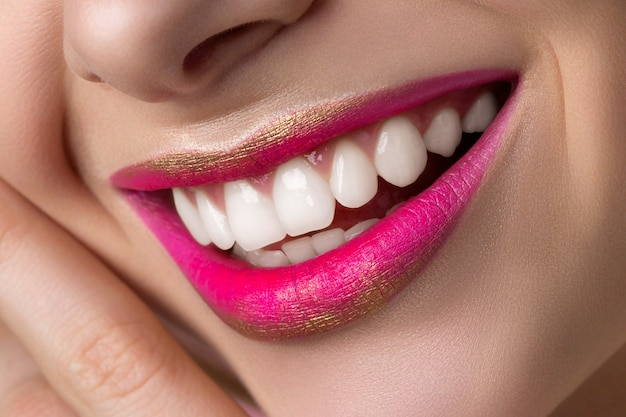 Close up view of beautiful smiling woman lips with fashion make up.