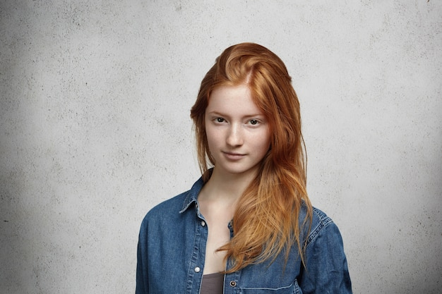 Close up view of beautiful young caucasian woman with ginger hair and freckles wearing stylish clothes looking  with faint smile, posing against gray wall.
