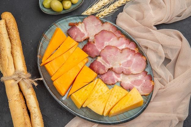 Vista ravvicinata dei migliori snack deliziosi per il vino su un asciugamano su uno sfondo scuro