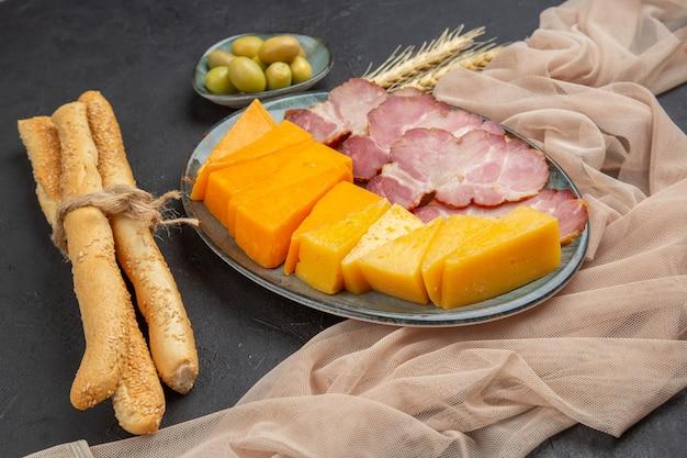 Vista ravvicinata dei migliori snack deliziosi per il vino su un asciugamano su un tavolo scuro