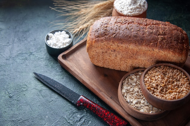 Vista ravvicinata di farina di fette di pane nero in una ciotola su tavola di legno e punte di coltello farina d'avena cruda di grano sul lato sinistro su sfondo invecchiato di colori misti