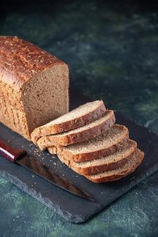 Vista ravvicinata del coltello per fette di pane nero su tavola di colore scuro su sfondo blu in difficoltà