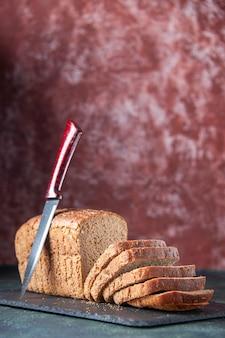 Vista ravvicinata del coltello per fette di pane nero su tavola di colore scuro su sfondo invecchiato di colori misti