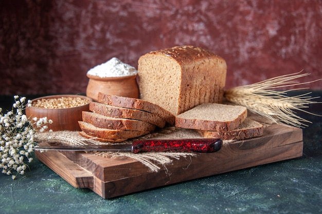 Close up view of black bread slices on nude color towel spikes flower on cutting boards on mixed colors background