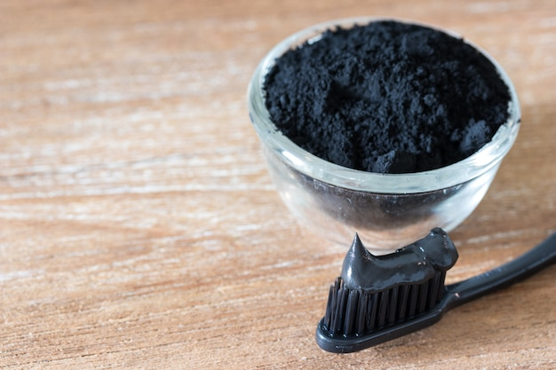 Close up view of black charcoal toothpaste and toothbrush ion wooden