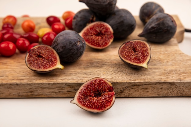 Close up view of black figs on a wooden kitchen board with cornelian cherries isolated on a white wall