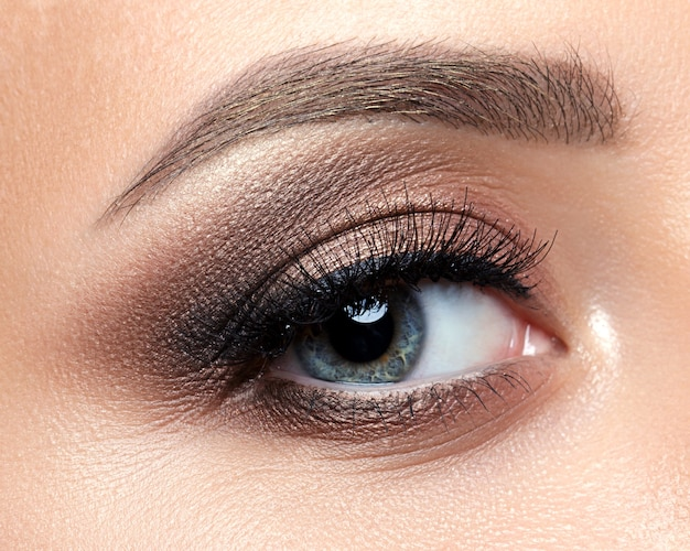 Close up view of blue woman eye with beautiful golden shades and black eyeliner makeup. classic make up. perfect brows.