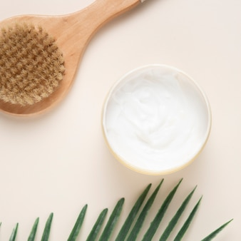 Close-up view of body cream and brush on plain background
