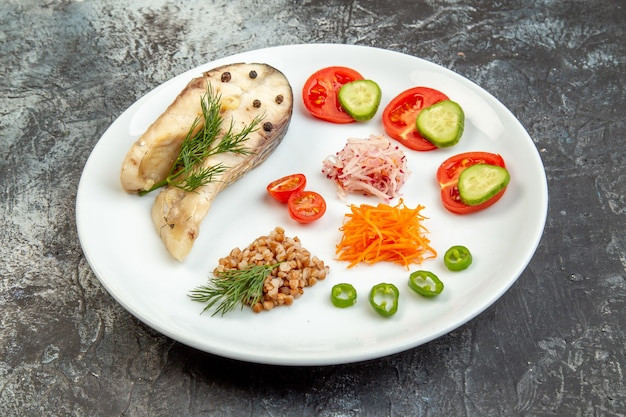 Vista ravvicinata del grano saraceno di pesce bollito servito con verdure verdi su un piatto bianco sulla superficie del ghiaccio con spazio libero