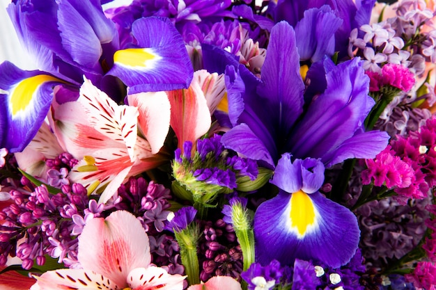 Close up view of a bouquet of pink and purple color alstroemeria lilac iris and statice flowers
