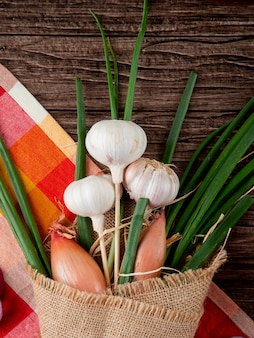 Close-up view of bouquet of vegetables as garlic green onion and shallot on cloth on wooden background