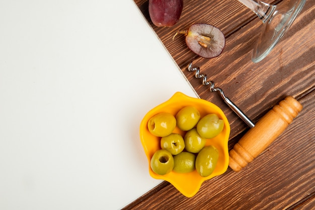 Close-up view of bowl of olive and note pad with grape corkscrew on wooden background with copy space