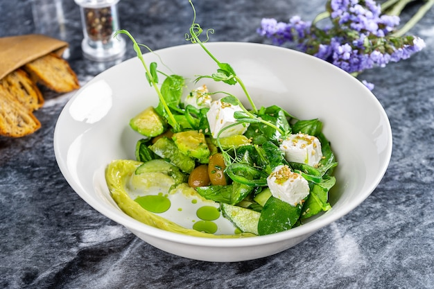 Close up view on bowl with green vegetables with feta salad