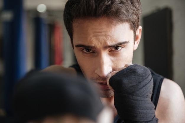 Chiuda sulla vista del pugile che fa l'esercizio in palestra