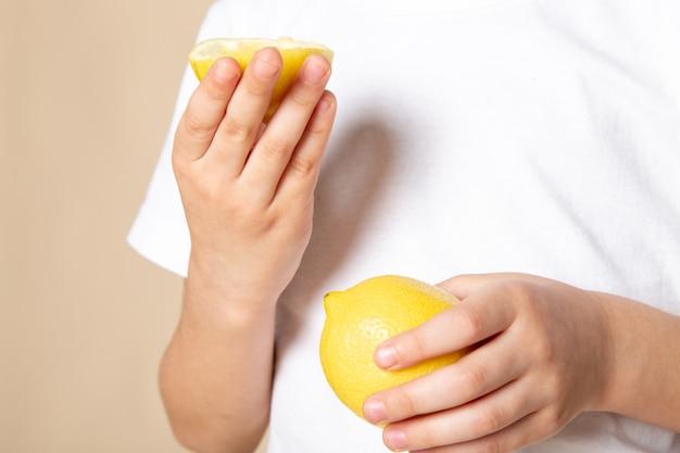 Vicino, vista ragazzo che tiene la fetta di limone