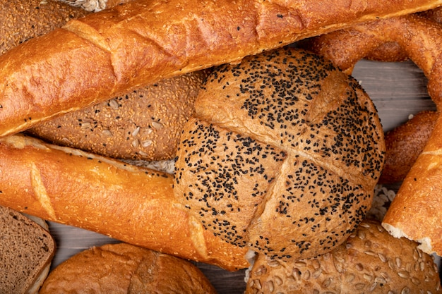 Close-up view of breads as poppy seed cob baguette bagel and others on wooden background