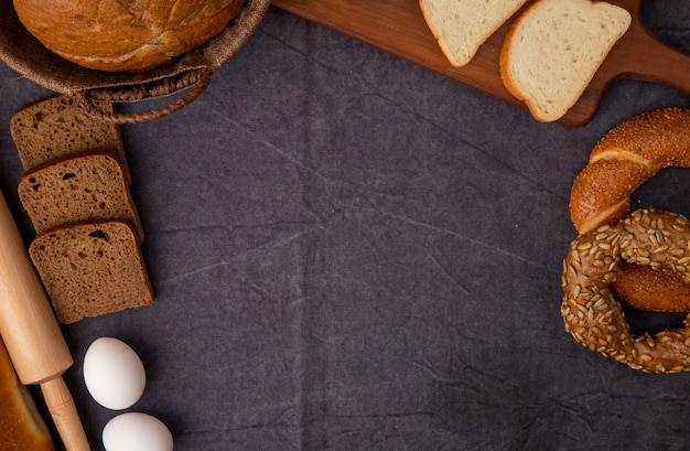 Close-up view of breads as rye bread cob white bread bagel with eggs and rolling pin on maroon background with copy space
