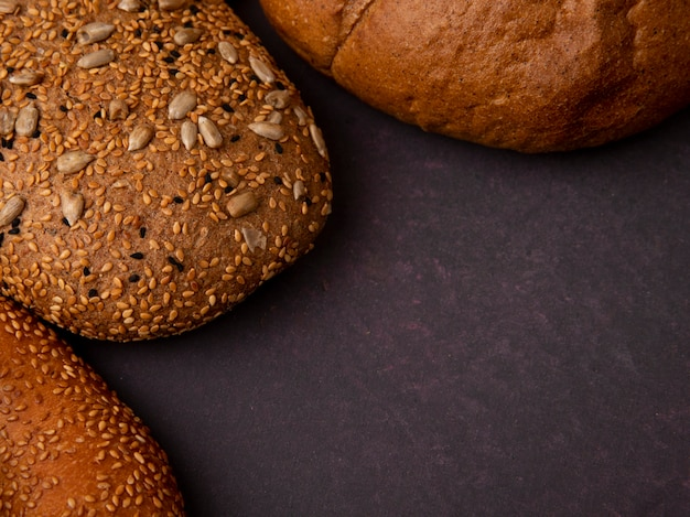 Close-up view of breads as seeded brown and classic cob bagel on maroon background with copy space