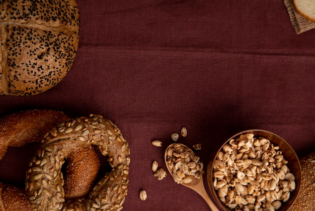 Close-up view of breads as seeded cob bagel with bowl of corns and spoonful of corns on burgundy background with copy space