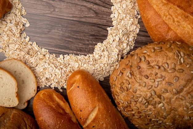Close-up view of breads as white baguette cob with oat-flakes on wooden background
