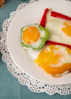 Close-up view of breakfast set plate with eggs and peppers on paper doily on blue background