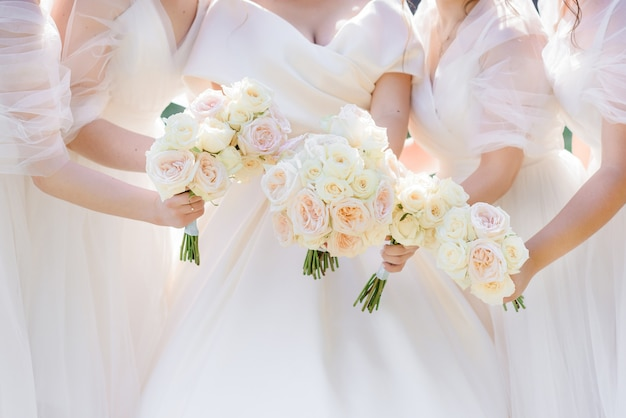 Close up view of bride and four bidesmaids holding beautiful trendy bouquets with fresh roses