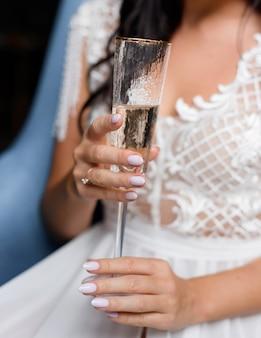 Vista ravvicinata della sposa con in mano un bicchiere di champagne, senza volto