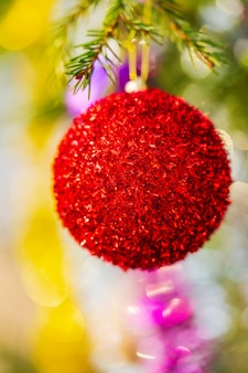 Close-up view of bright red christmas ball and shining tinsel hanging on branch of tree. xmas festive composition for happy new year. selective focus in foreground, blurry bokeh in background.