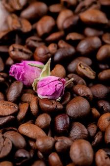 Chiuda sulla vista dei chicchi di caffè marroni e dei germogli rosa del tè