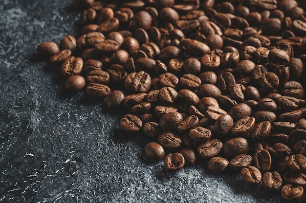 Close up view of brown coffee seeds on dark