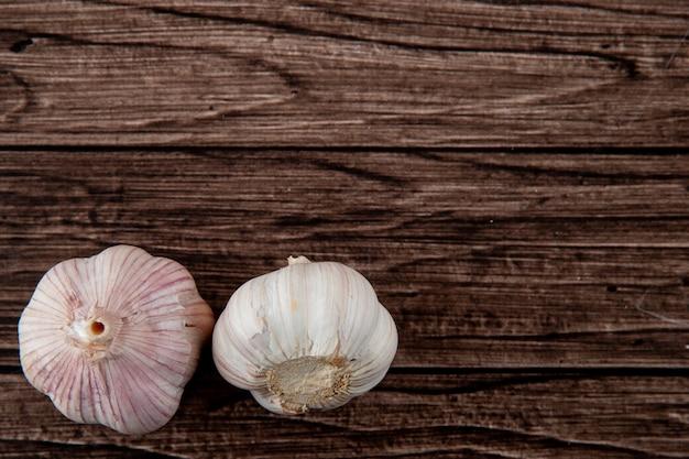Vista del primo piano delle lampadine di aglio dalla parte di sinistra e del fondo di legno con lo spazio della copia