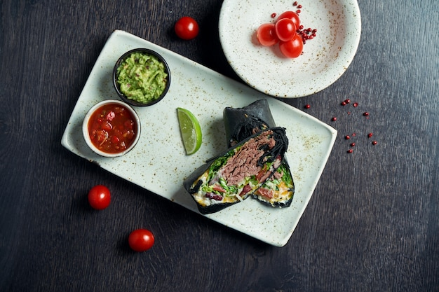 Close up view on burrito with beef, rice, tomatoes, corn and bell pepper in black pita on a brown plate with tomato salsa and guacamole. vegetarian shawarma roll