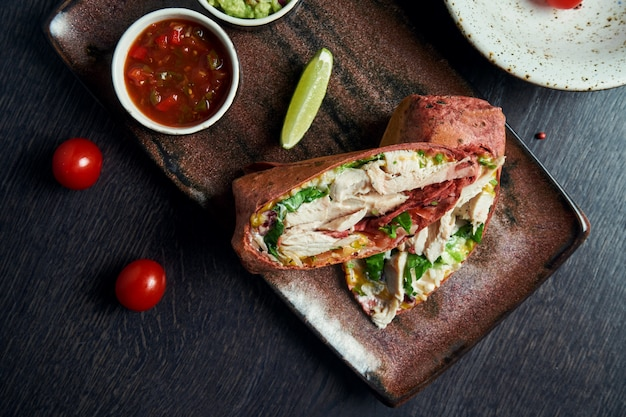 Close up view on burrito with chicken, rice, tomatoes, corn and bell pepper in brown pita on a brown plate with tomato salsa and guacamole. vegetarian shawarma roll