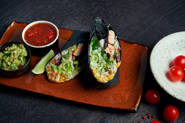 Close up view on burrito with salmon, lettuce, rice, tomatoes, corn and bell pepper in black pita on a brown plate with tomato salsa and guacamole. vegetarian shawarma roll