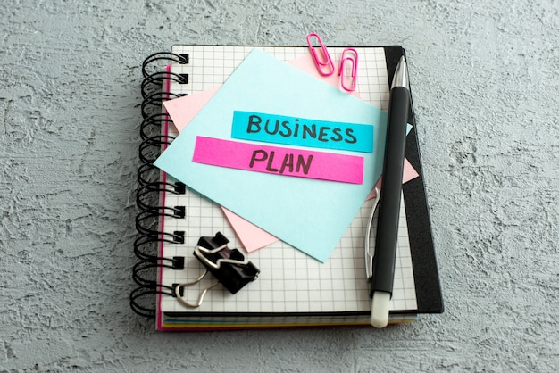 Close up view of business plan on coloured envelopes on spiral notebook and book on gray sand background