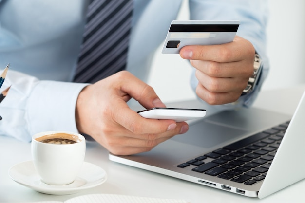 Close up view of businessman hands holding credit card and making online purchase using mobile phone. shopping, consumerism, delivery, financial security, anti-fraud or internet banking concept.
