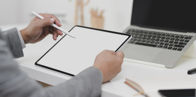 Close-up view of businessman writing his plan on blank screen tablet in his modern office