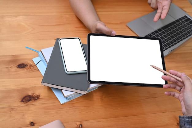 디지털 태블릿을 사용하고 사무실에서 비즈니스 데이터를 분석하는 비즈니스맨을 닫습니다.