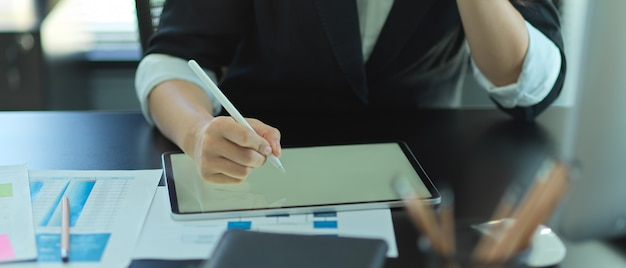 Close up view of businesswoman working with tablet and paperwork on office desk