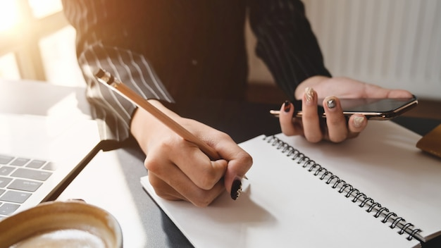 Close up view of businesswoman writing on notebook in comfortable workplace
