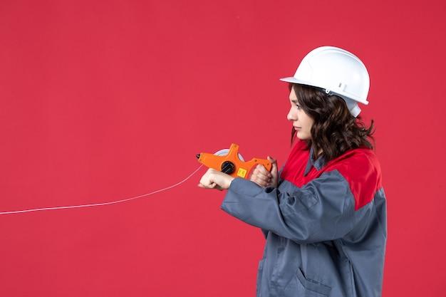 Chiuda sulla vista dell'architetto femminile occupato in uniforme con nastro di misurazione di apertura del cappello duro sulla parete rossa
