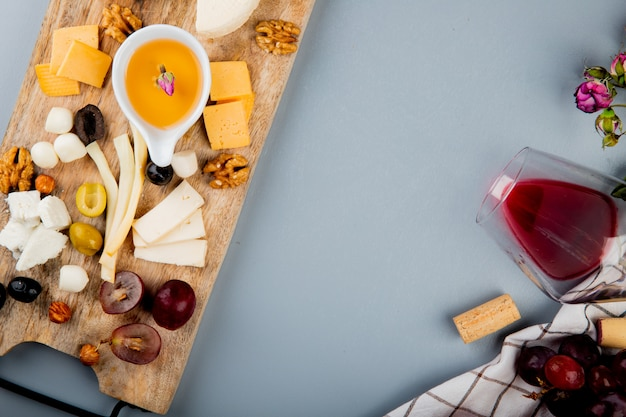 Close-up view of butter with cheese grape olive nuts on cutting board and glass of wine corks flowers on white with copy space