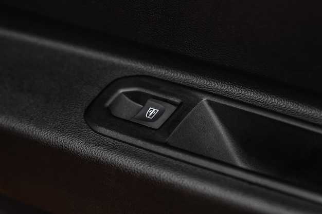 Close up view of button controlling window in modern car interior. vehicle interior detail. door handle with windows controls