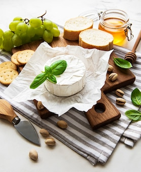 Close up view of camembert cheese, grape, nuts and honey on cutting board on white tabletop