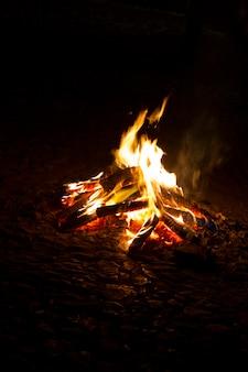 Close up view of a campfire at night.