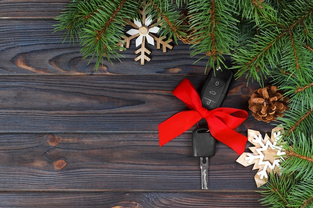 Close-up view of car keys with red bow as present on wood