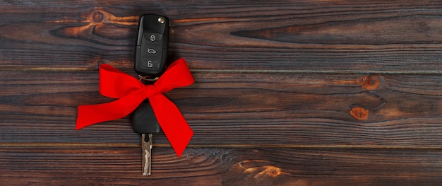 Close-up view of car keys with red bow as present on wooden background